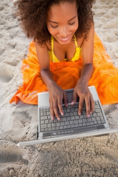 Afrikanerin mit Laptop am Strand